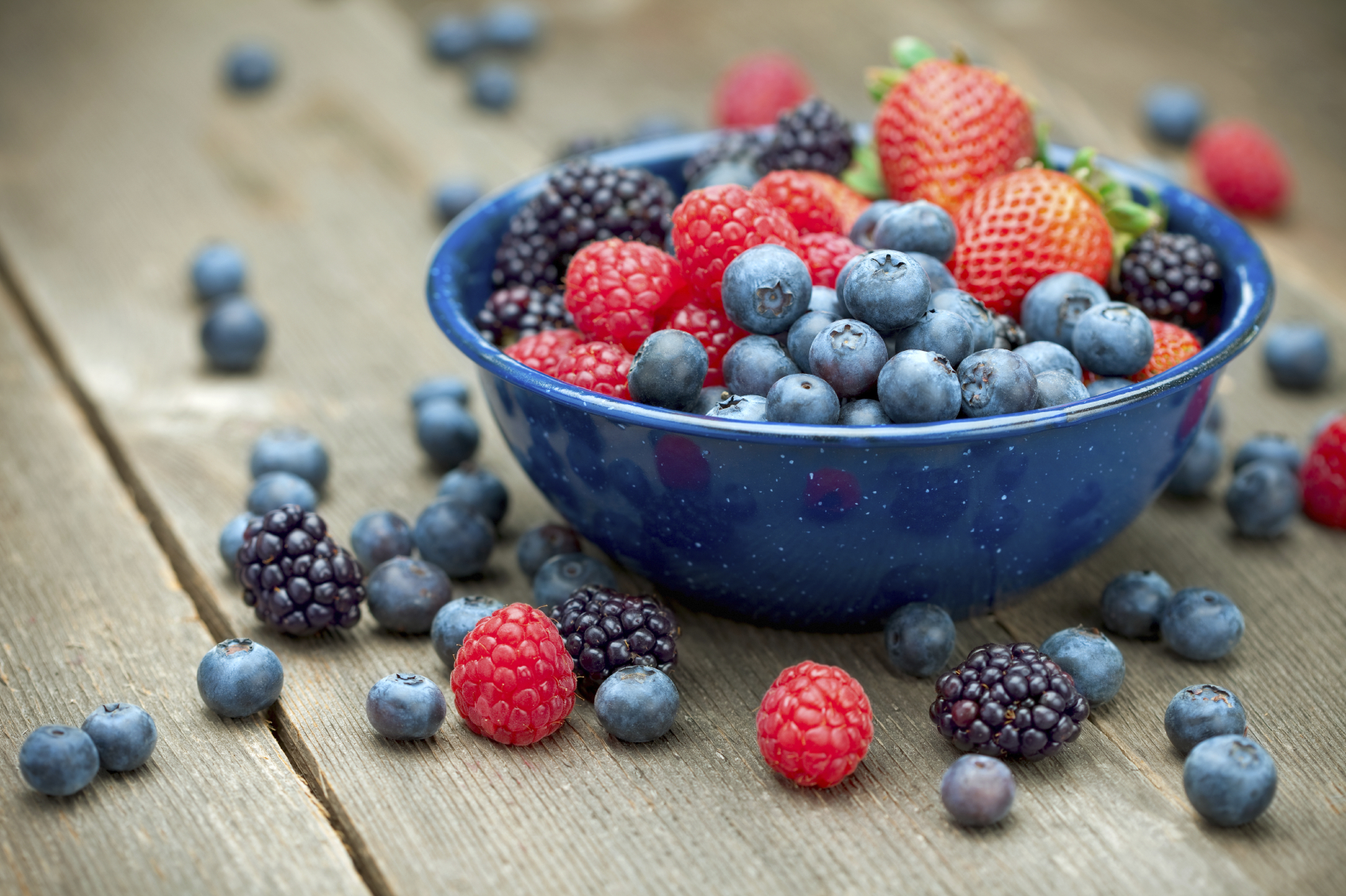 A bowlful of delicious organic berries. Strawberries, blackberries, blueberries and raspberries. Shallow dof